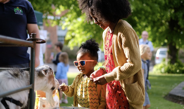 two young girls stroking a goat at a fair