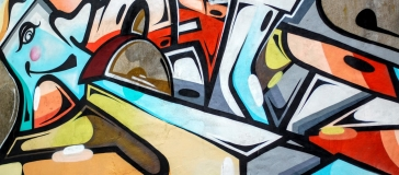 graffiti of faces and shapes in bright colours
