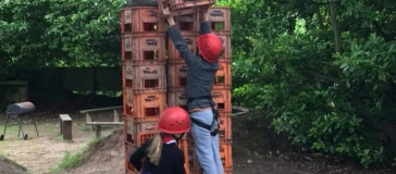 Two children wearing a harness and helmet stood in front of a stack of crates. One is handing a crate up in the air towards the top of the stack.