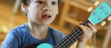Primary age boy with dark tossled hair and missing teeth, holding an aqua ukulele. He's sat cross legged on the floor with a look of concentration on his face.