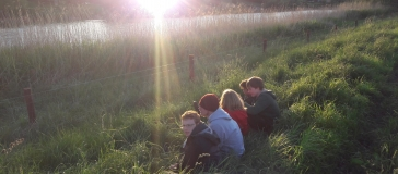 Four young people sat in a line together on long grass in the foreground, overlooking a river reflecting a low sun in the background