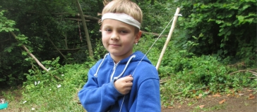 Child with short hair is stood wearing a blue hoody and white bandana holding a bow over their shoulder. Stood in a wooded clearing.