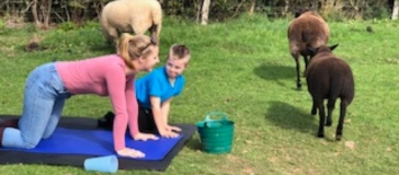 An adult and child on all fours on a yoga mat in a field surrounded by two black sheep and one white sheep