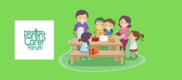 children sit around a picnic table smiling