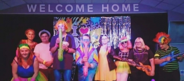 group of people in disco clothing, text above them reads 'welcome home'
