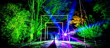 A dark night is brightened by a landscape of trees brightly lit up in greens, oranges and blue. A woman and her two young children stand between a square arch of light. A bright spot light shines from behind them.