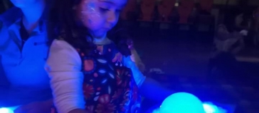 child holding a tray with glowing bubbles