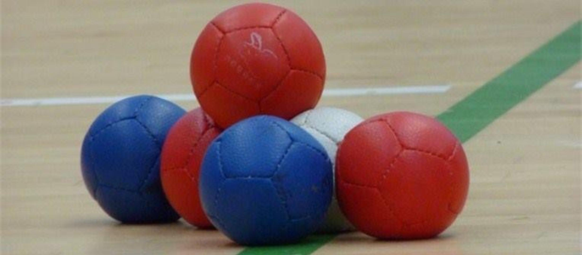 A group of 5 boccia balls, two blue, two red and one white with another red ball balanced on top