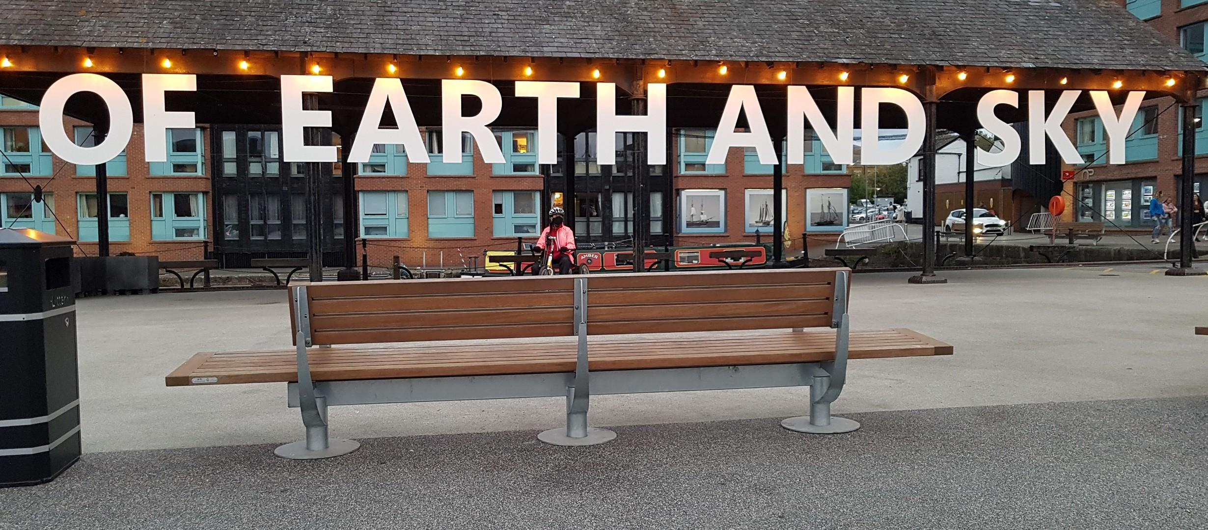 bench with the words 'of earth and sky' hanging in big letters from a roof behind