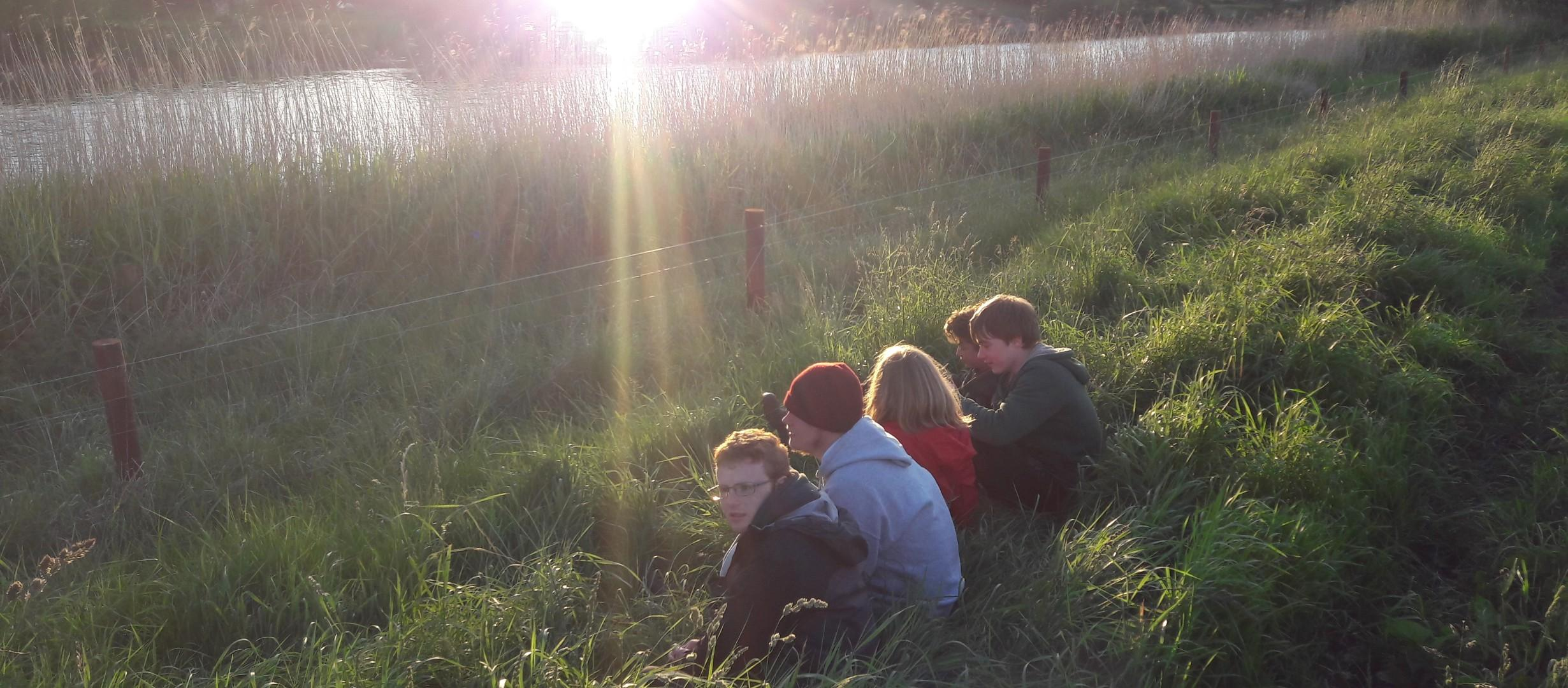 Four young people sat in a line together on ,long grass in the foreground, overlooking a river reflecting a low sun in the background