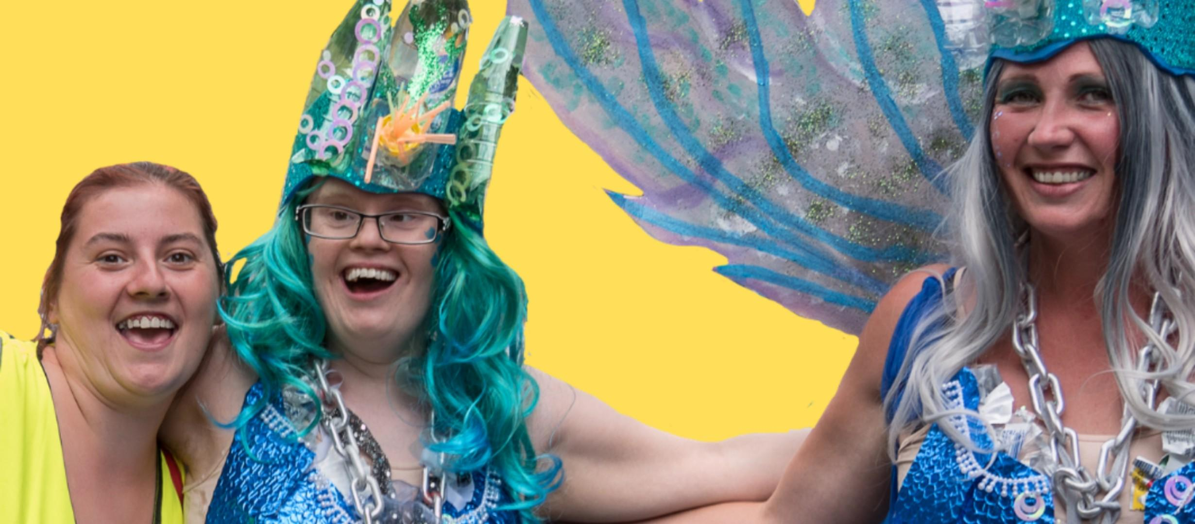 Two individuals smiling at the camera. Two are dressed in blue carnival outfits including crowns and a wing structure. The middle individual has blue curly long hair. The third person is smiling at the camera wearing a yellow top.