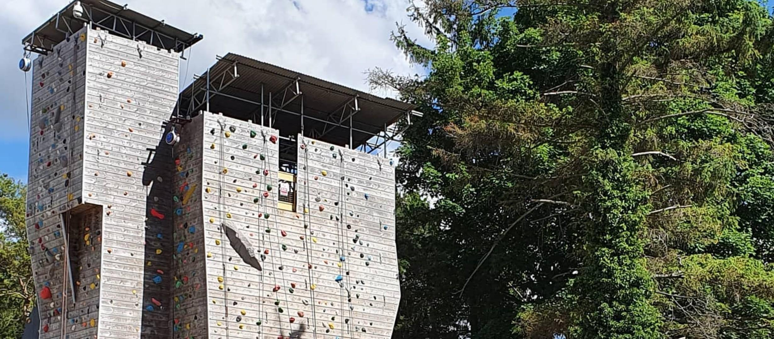two climbing walls outside by trees