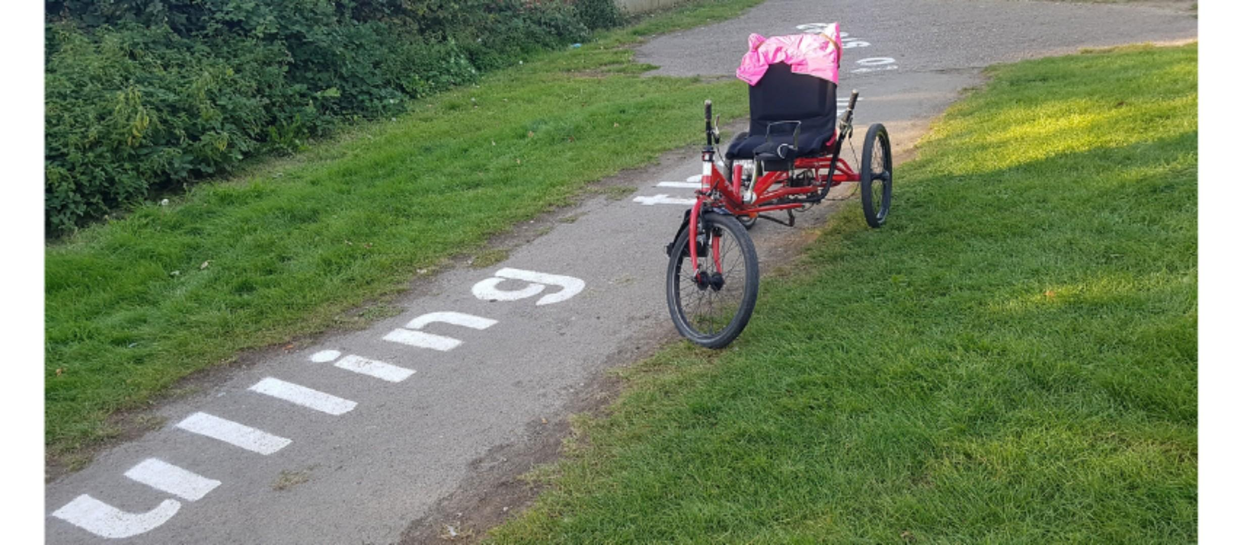 recumbent trike on pathway by grass, words on pathway, only visible word 'lulling'