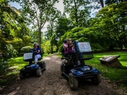 2 women on scooters on a hard path in the arboretum