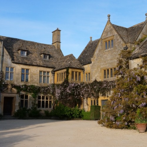 The Manor House at Hidcote Gardens, a traditional Cotswold Manor House with Cotswold yellow brick, with a wisteria growing up the right corner of the picture and a graveled yard leading up to the house.